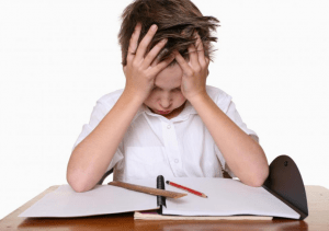 Image of a boy with his head in his palms, looking at a notebook.