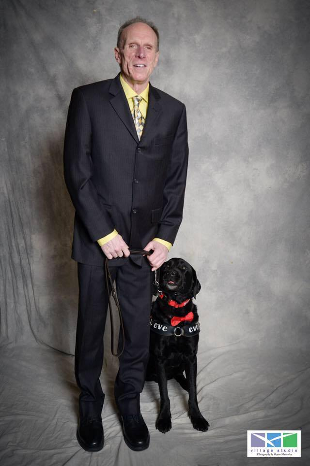 Man wearing a black suit, holding the leash of a Labrador guide dog