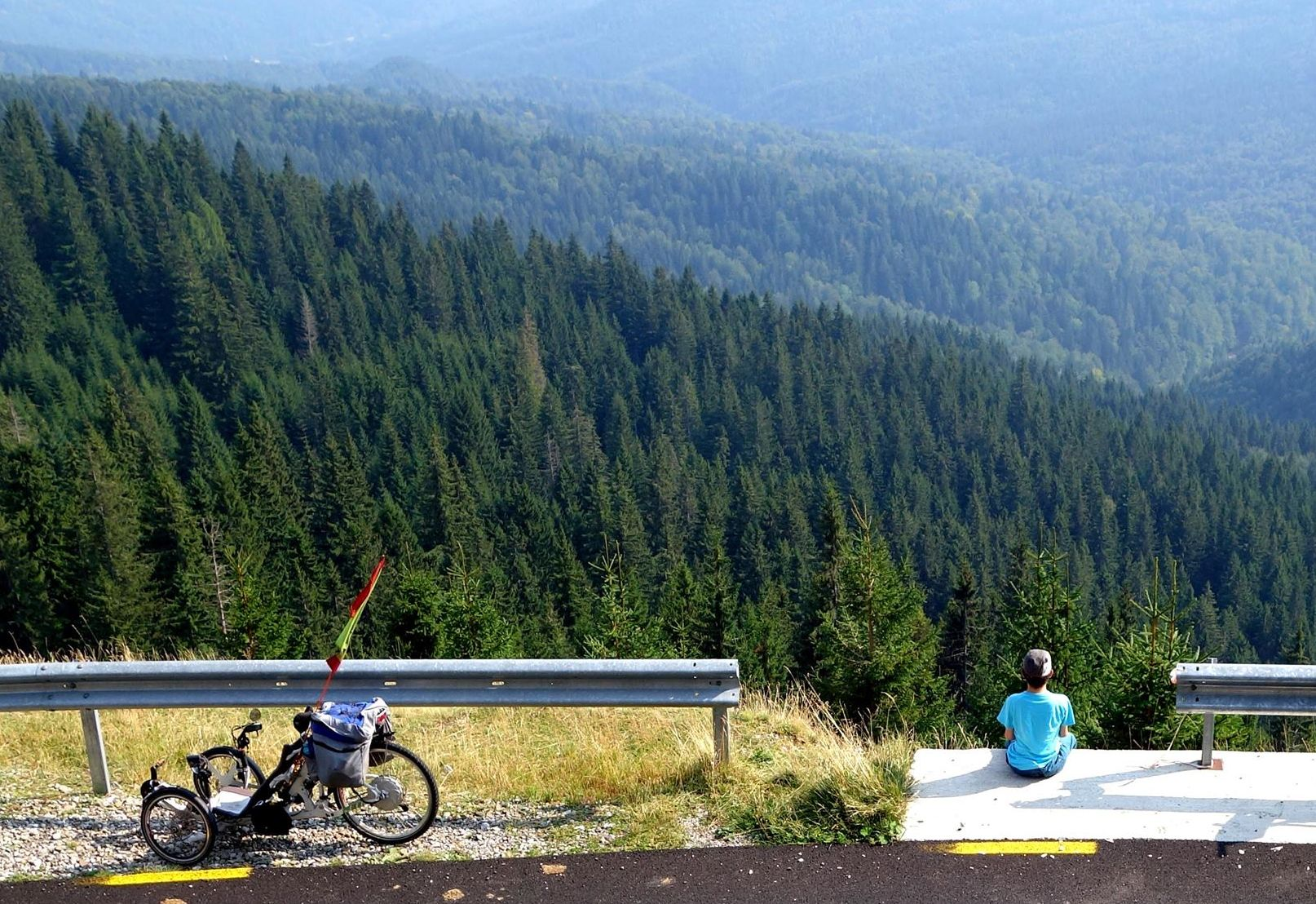 A man sits at the edge of a suspended highway overlooking forests. A trike is parked close to him.